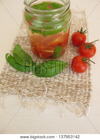 Detox water with tomato and basil leaves