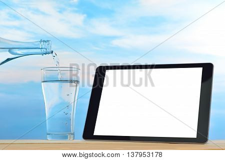 Tablet computer with blank white screen on pile of coffee beans