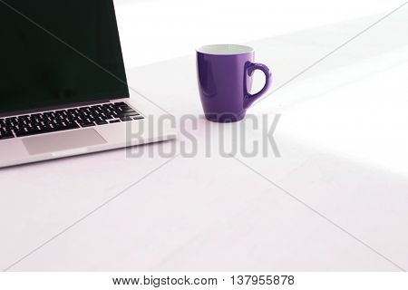 Close up of laptop computer and Purple mug