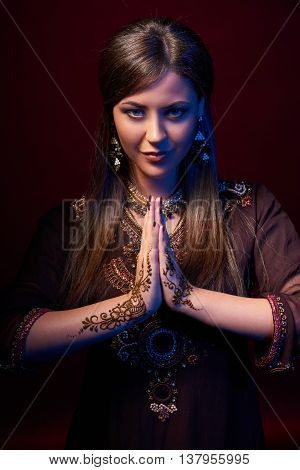 Fine art portrait of beautiful fashion Indian woman with oriental dress, accessories and mehndi henna tattoos with hands clasped together praying