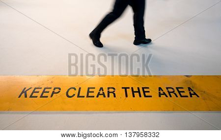 Man walking in prohibited area with motion blur breaking rule concept keep clear sign on the floor with copy space