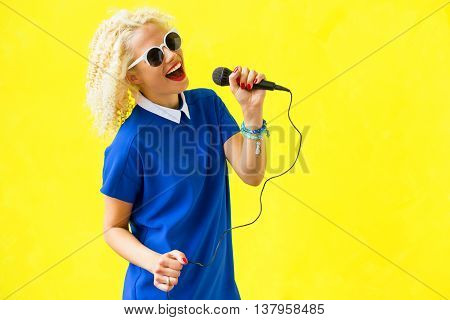 Funky woman singer  singing and using microphone