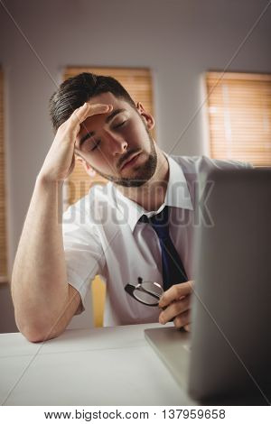 Tired young man with eyes closed in office