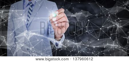Midsection of businessman writing with marker against dark background