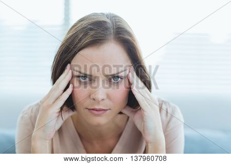 Portrait of young woman suffering headache at home