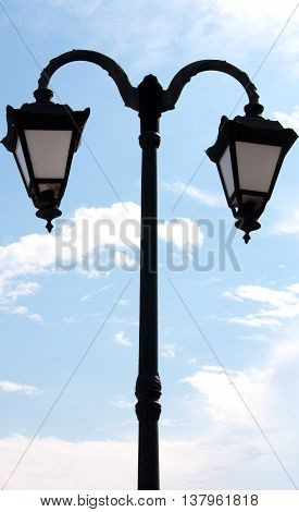 vintage lighting pole with twin double lamp lantern on background of blue sky