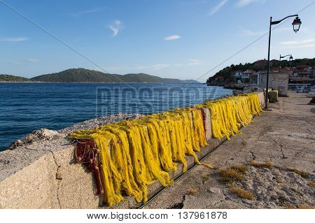 Yellow fishnet drying in the sunlight port and houses