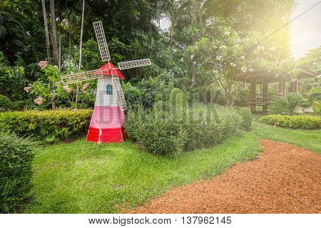 Green garden decorated by small colorful lighthouse wind turbine with soft sunlight from sky