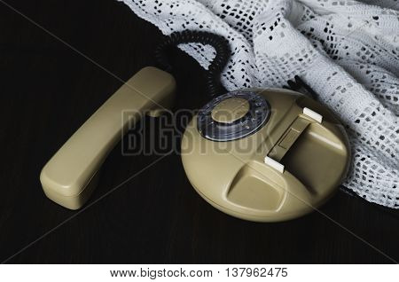 Old-fashioned Phone On Knitted Napkin On A Dark Wooden Table. Top View, Horizontal