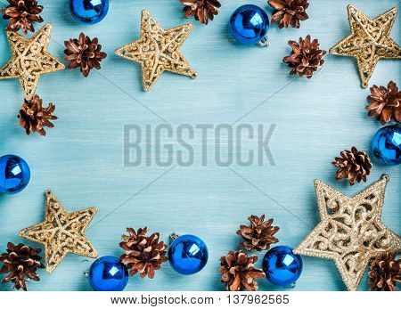 New Year or Christmas background: golden stars, blue glass balls and cones over blue painted wooden backdrop, top view, copy space