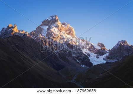 Most beautiful mountain in the Caucasus. Top of Ushba at dawn. Pure morning sky. Beauty in nature. Main Caucasian ridge. Zemo Svaneti, Georgia