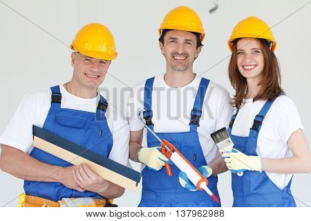 Three smiling workers wearing hardhats with different tools