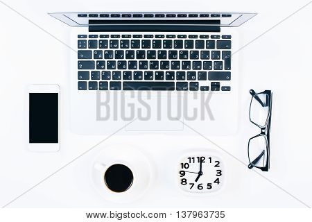 Top view of bright office desktop with blank cellular phone coffee cup clock glasses and laptop. Mock up