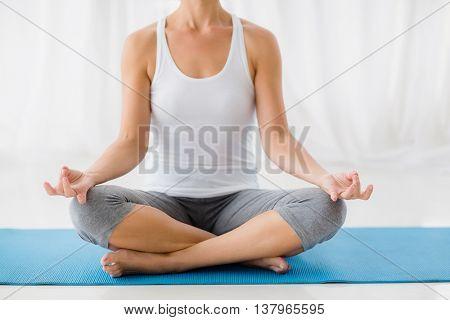 Woman performing yoga at fitness studio