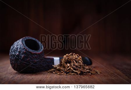 Smoking pipe and tobacco on a wooden table