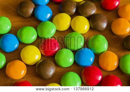 Colorful Sweet Chocolate Buttons On Wooden Background