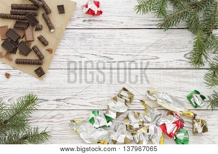 Christmas Card with chocolate candies wrappers and fir branches on white wooden background. Copy space composition.
