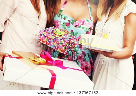 Midsection of women holding birthday cake and presents