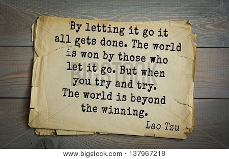 Ancient chinese philosopher Lao Tzu quote on old paper background.  By letting it go it all gets done. The world is won by those who let it go. But when you try and try. The world is beyond  winning.