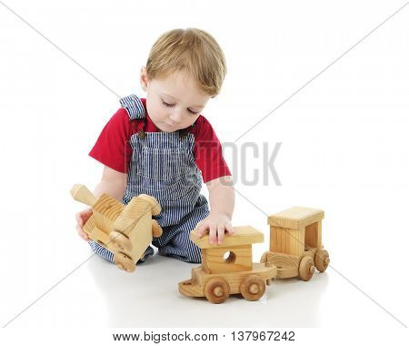 An adorable 2-year-old in his engineer overalls, attempting to attach the toy wooden engine to its cars.  On a white background.