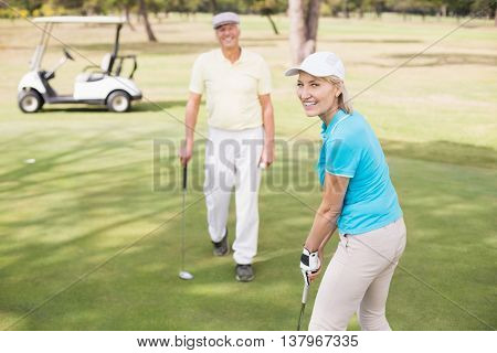 Portrait of confident golfer woman by man standing on field