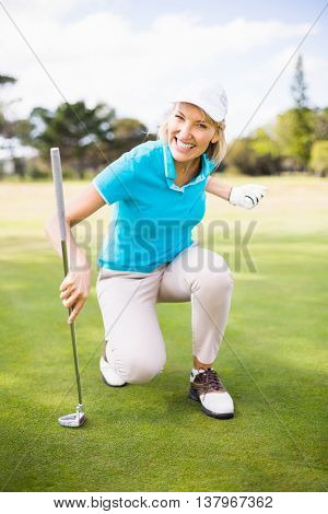 Portrait of smiling golfer woman clenching fist