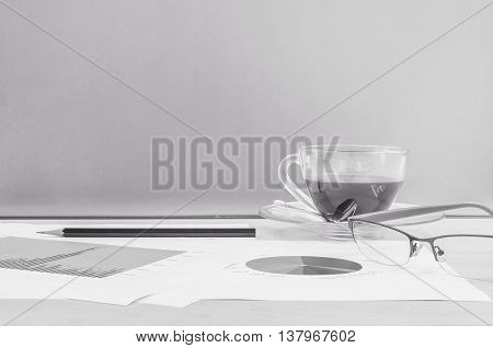 Closeup black coffee in cup of coffee with work paper and pencil and eyeglasses on blurred desk and glass wall textured background work concept by coffee and work paper in black and white tone