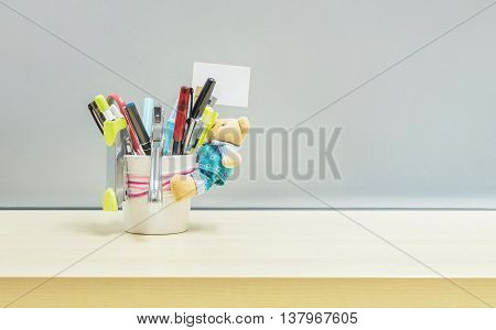 Closeup office equipment and color pen in desk tidy cup for pen on blurred wooden desk and frosted glass wall textured background in the work office