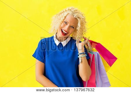 Excited woman after shopping holding many shopping bags