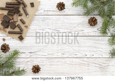 Christmas Card with chocolate candies and fir branches on white wooden background. Copy space composition.
