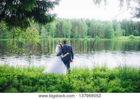 bride and groom standing in front of the lake and looking into the distance.