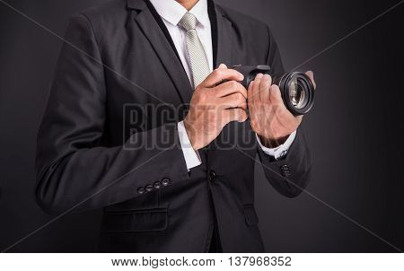 Young photographer man holding camera isolated on black background