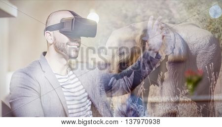 Side view of an elephant in the savanna against male graphic designer wearing virtual glasses