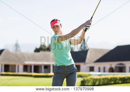Golfer woman taking shot while standing on field