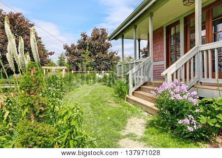 Backyard Of Big Farmhouse With Beautiful Flowerbed