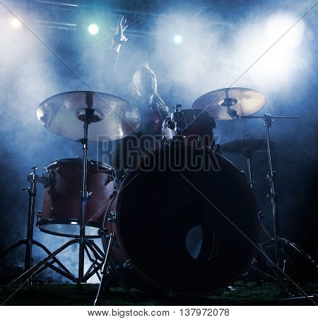 Silhouette of the drummer on stage. Dark background smoke spotlights