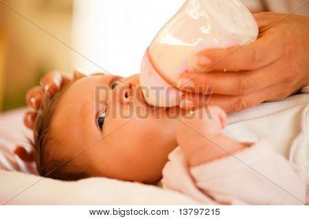 Madre está alimentando a su bebé con un biberón; escena muy tranquilo