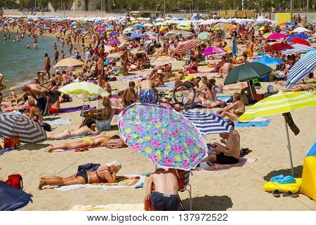 BARCELONA, SPAIN - JULY 10: People sunbathing at Nova Icaria Beach on July 10, 2016 in Barcelona, Spain. This busy beach is mainly frequented by the locals