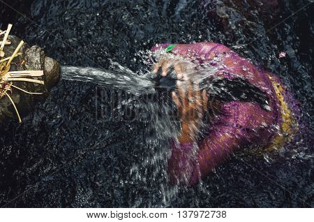 A shot of a person bathe in holy water at Tampaksiring Temple Ubud Bali Indonesia. It is believed that bathing in this water may receive forgiveness and spiritual cleansing.