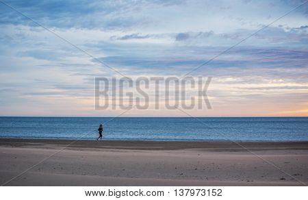 Valencia, Spain - JAN 6, 2016: Women running on the beach with the sea in the background