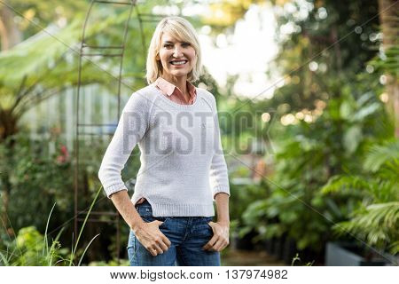 Portrait of confident mature woman standing at greenhouse