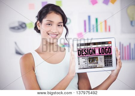 Happy businesswoman showing digital tablet in creative office against webpage for create a logo