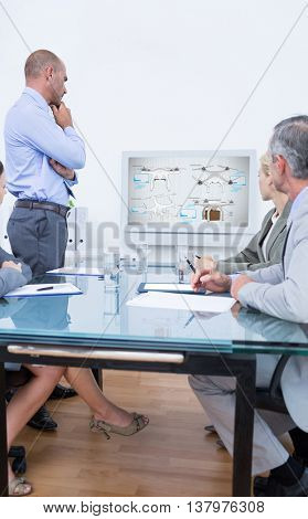 Business team looking at white screen against composite image of four drones