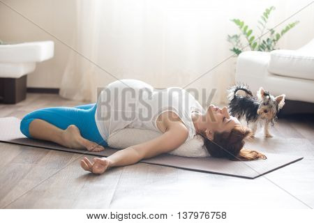 Pregnant Woman And Her Pet Dog Doing Yoga At Home
