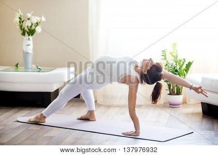 Pregnant Woman Doing Camatkarasana Yoga Pose At Home
