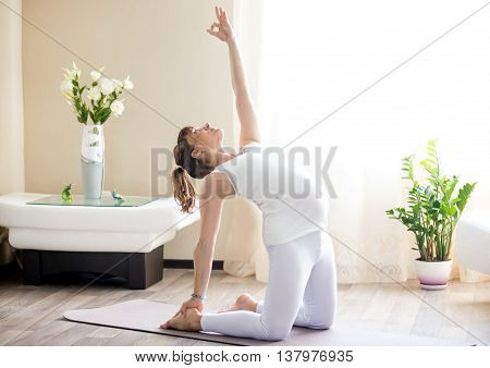 Pregnant Woman Doing Ustrasana Yoga Pose At Home