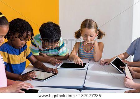 Multi ethnic children using digital tablets in classroom