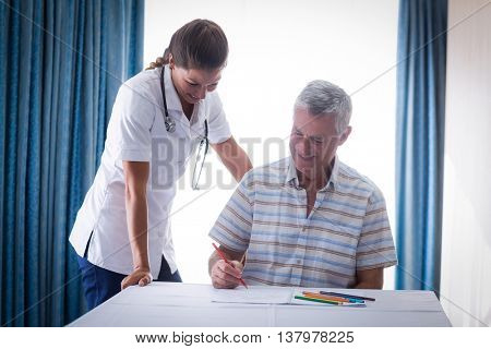 Doctor assisting a senior man while drawing in drawing book at home