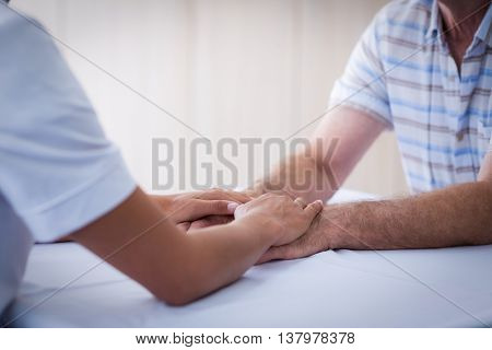 Mid section of female doctor consoling senior man in living room at home