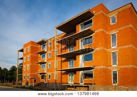 Multifamily building of red brick under construction.
